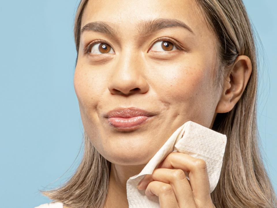 A woman with a smirk wipes her jaw with a wipe