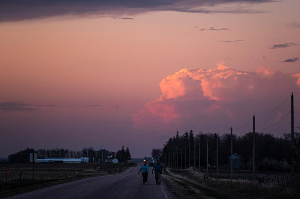 Two people walk down a rural road beside power lines under a cloudy sunset sky.