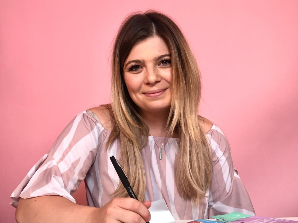 Steenbakkers, dressed in pink, sits at a desk in front of pink wall.