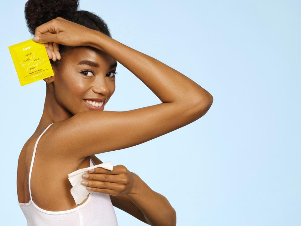 A woman holds one wipe over her head and wipes her armpit with another.