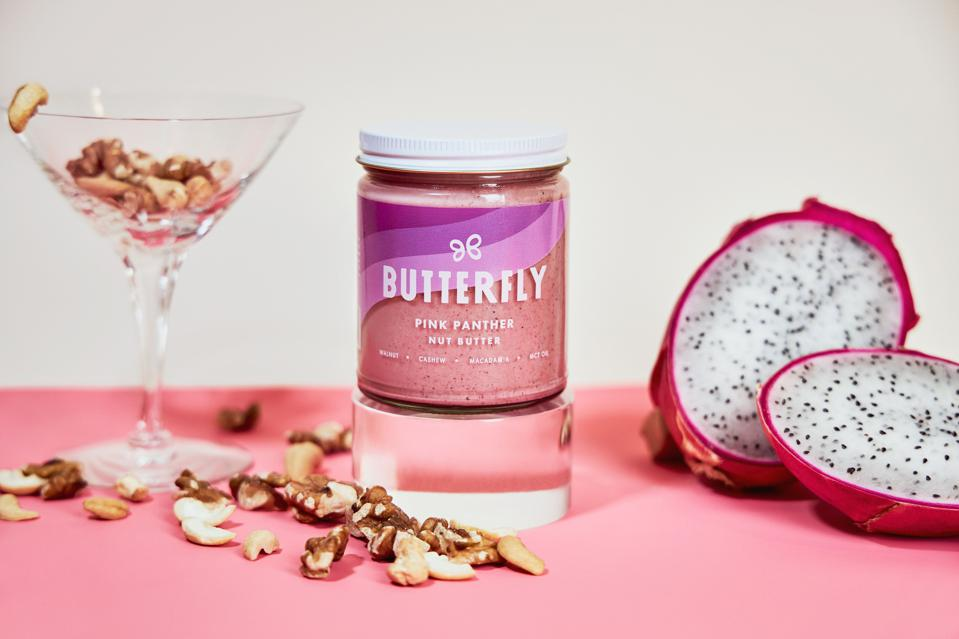 Butterfly's new Pink Panther Nut Butter next to a cocktail glass of nuts and dragon fruit.