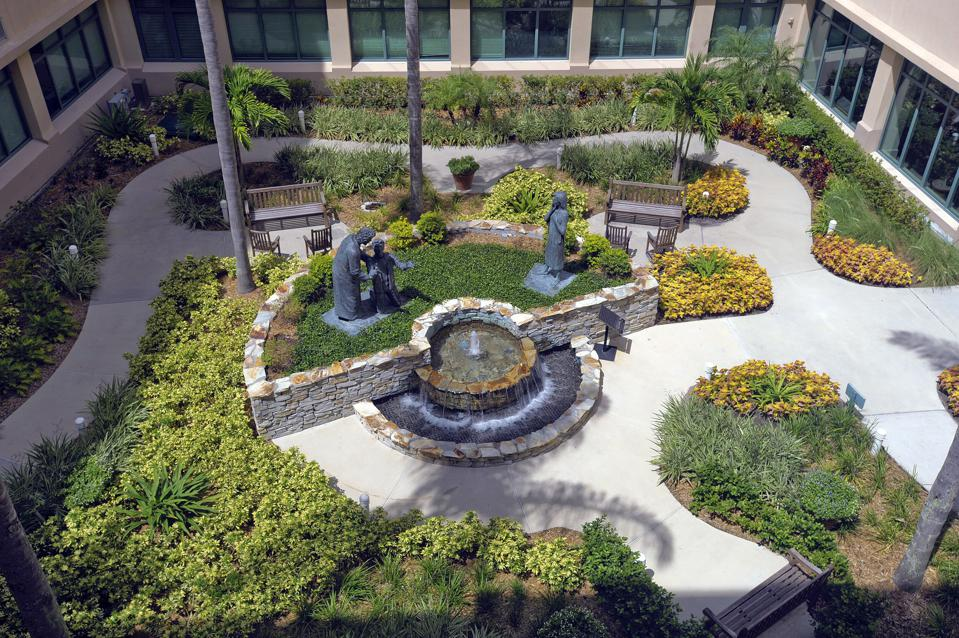 An aerial perspective of the hospital garden with several benches, plants, and statues.
