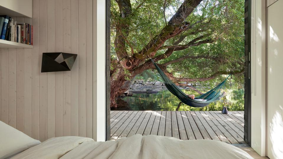 A bedroom with a view of water and trees surrounding it.