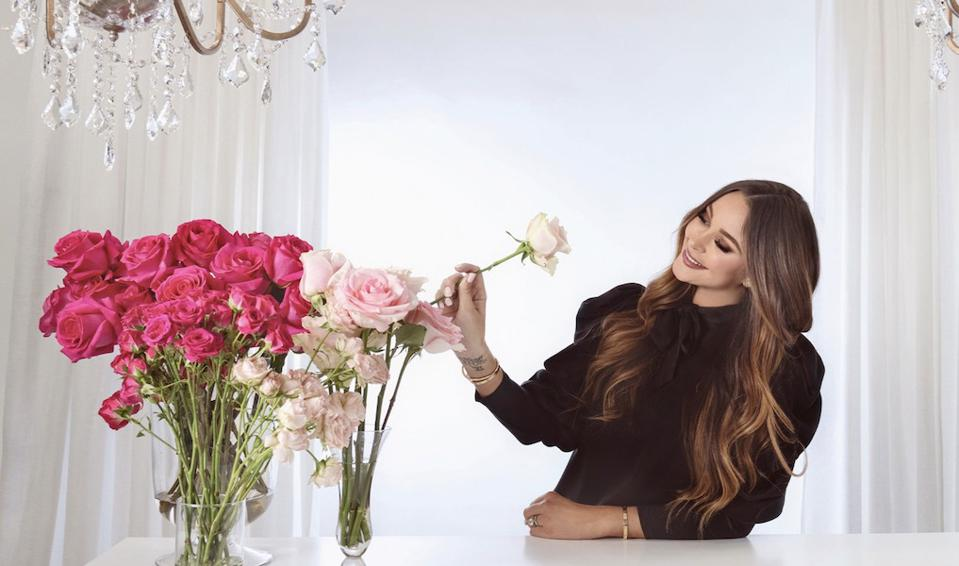Brunette stands at a table with pink roses in a vase