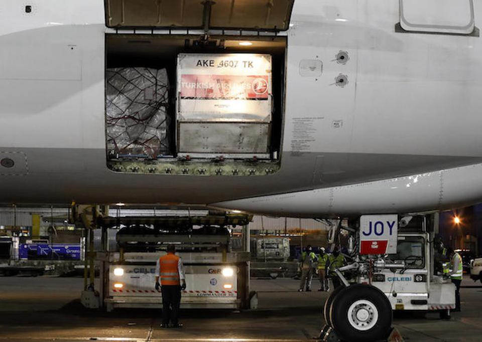 At the Indira Gandhi International Airport in New Delhi on May 18, 2021, ground staff prepare to unload a cargo plane filled with COVID-19 medical supplies sent by UNICEF.