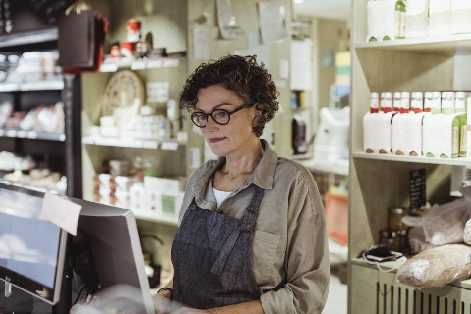 Confident sales woman working on computer in deli store