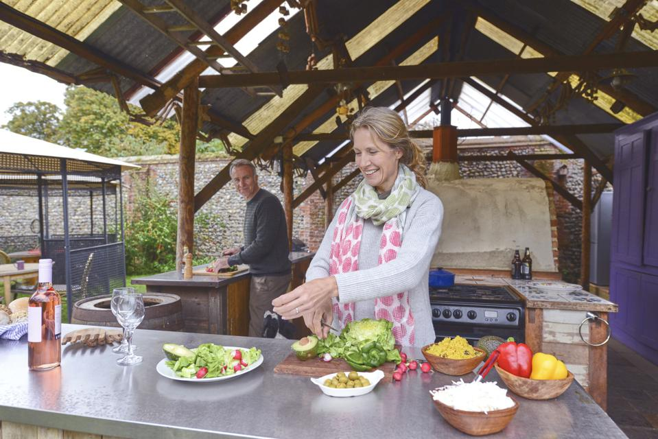 Mature married couple cooking together in outdoor kitchen.