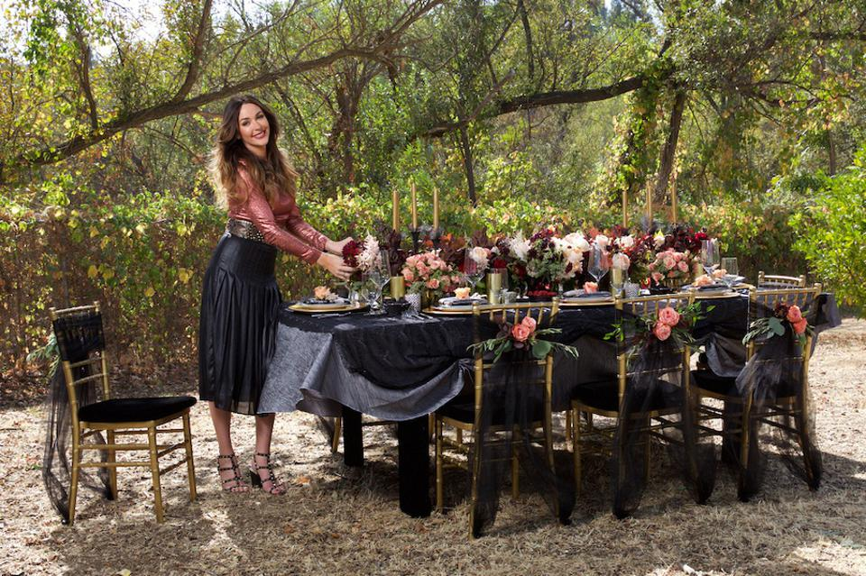 A brunette stands next to a stable that has candles, placesettings, flowers and a black tablecloth