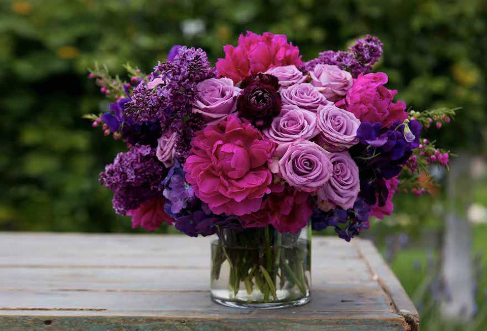 A Bouquet Box arrangement, various pink and purple flowers in a lucite vase on a wood table
