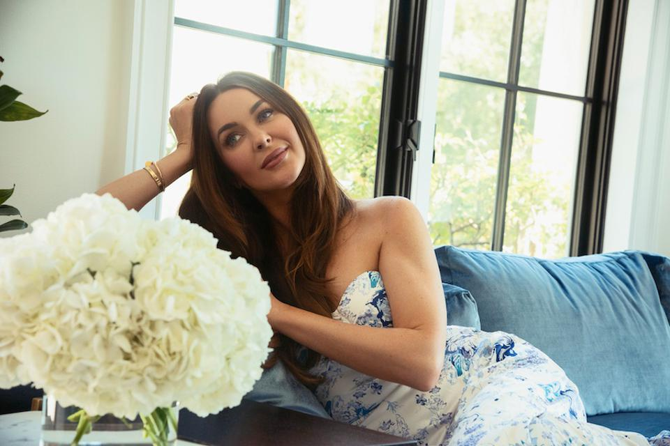 Brunette on a sofa next to a low flower vase