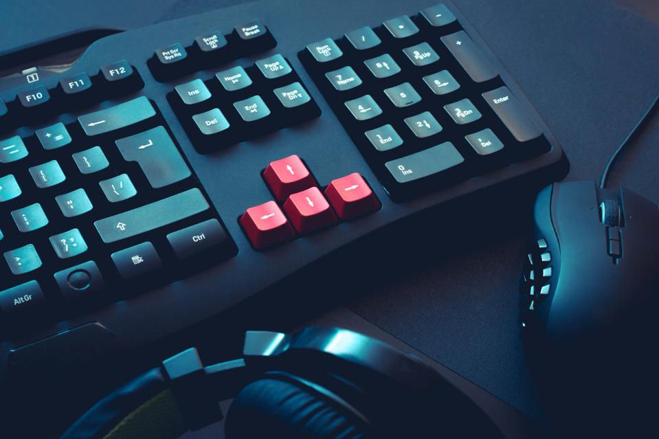 A picture of a gaming keyboard, headphones and mouse on black table
