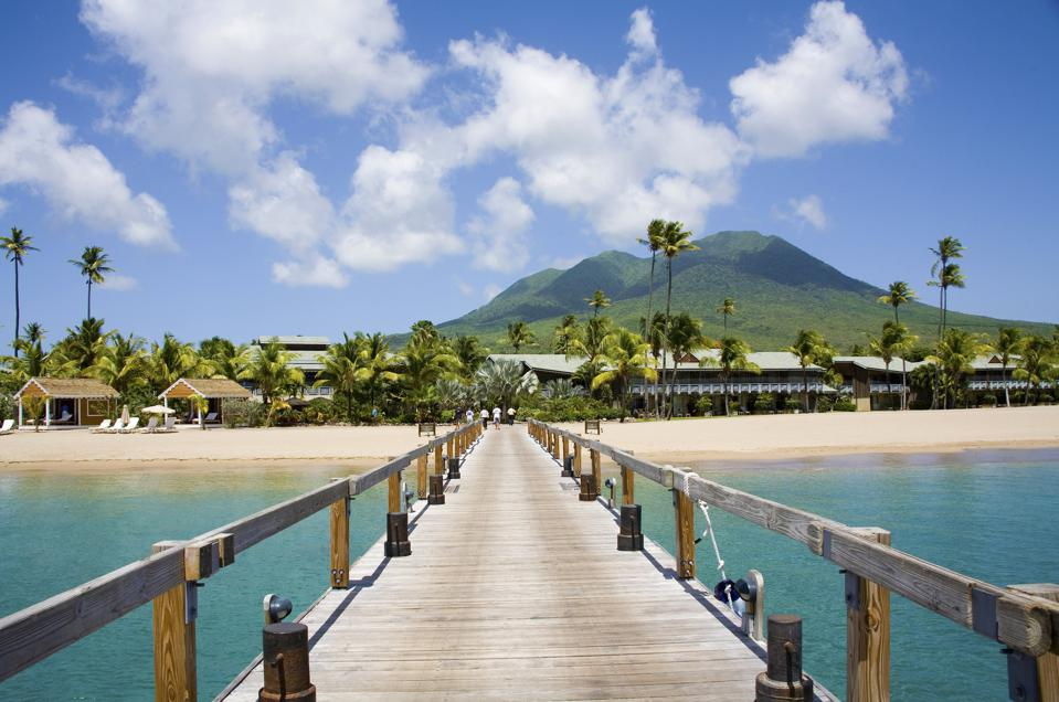 From the point of view of a person standing on a long wooden dock, view of Pinney's Beach with its white sands and coconut palms, with the Nevis volcano in the distance.