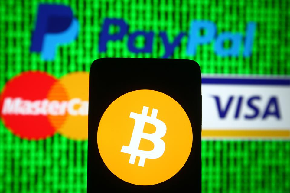 In this photo illustration a Bitcoin sign is seen on a...
