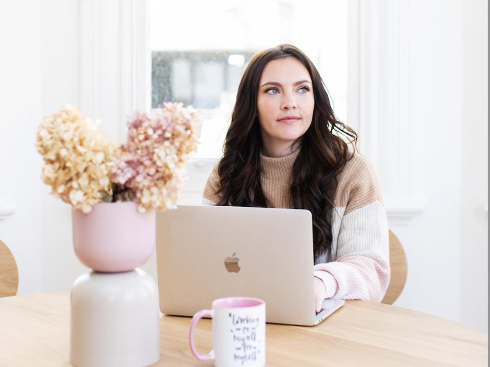 Norris sits at a desk with her laptop and pink flowers.