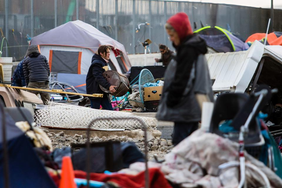 Homeless individuals gather their belongings before the city...