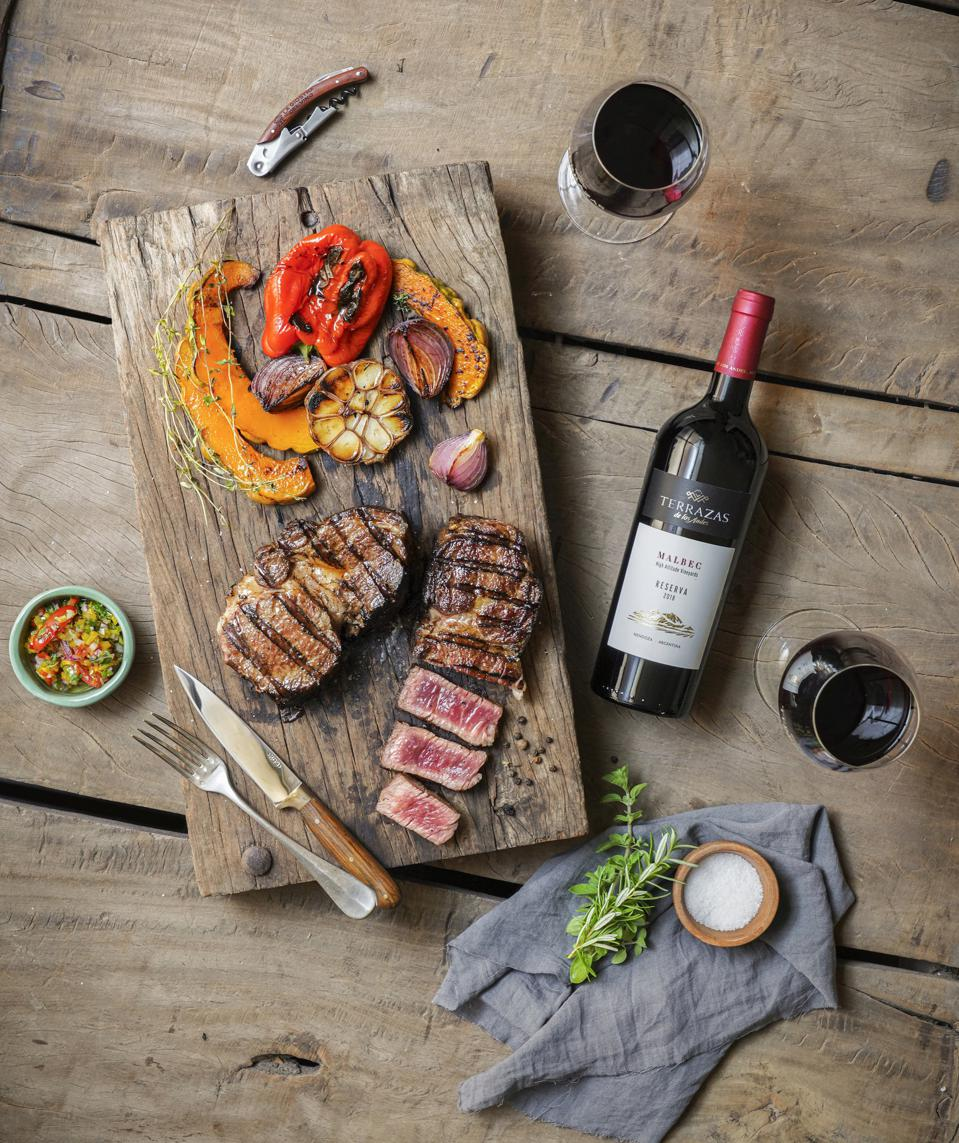 Terrazas de los Andes Malbec on table with glasses and grilled steak and fixings