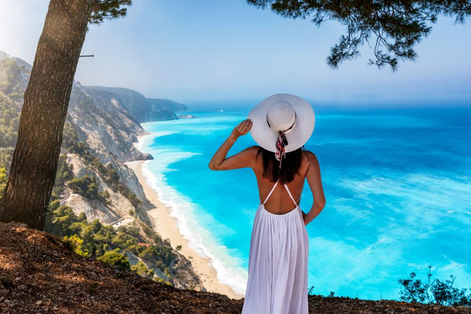 A woman stands on a viewing point over the turquoise sea of Egremni Beach, Lefkada, Greece