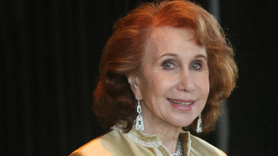 An older woman with red hair wearing diamond earrings and a gold jacket.
