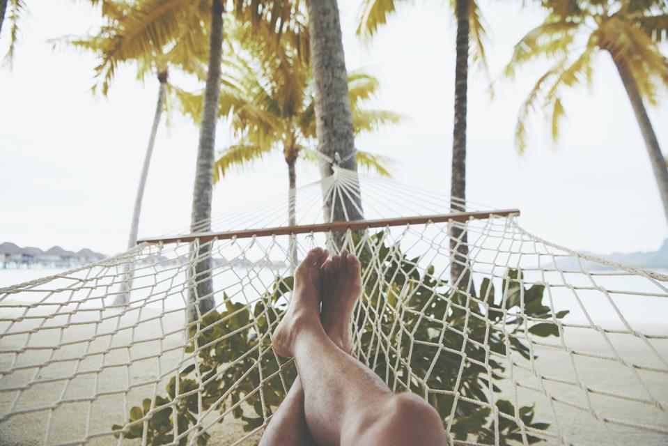 Relaxing feet on a beach hammock.