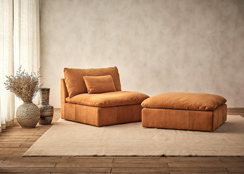 A brown leather chair and ottoman in a living room