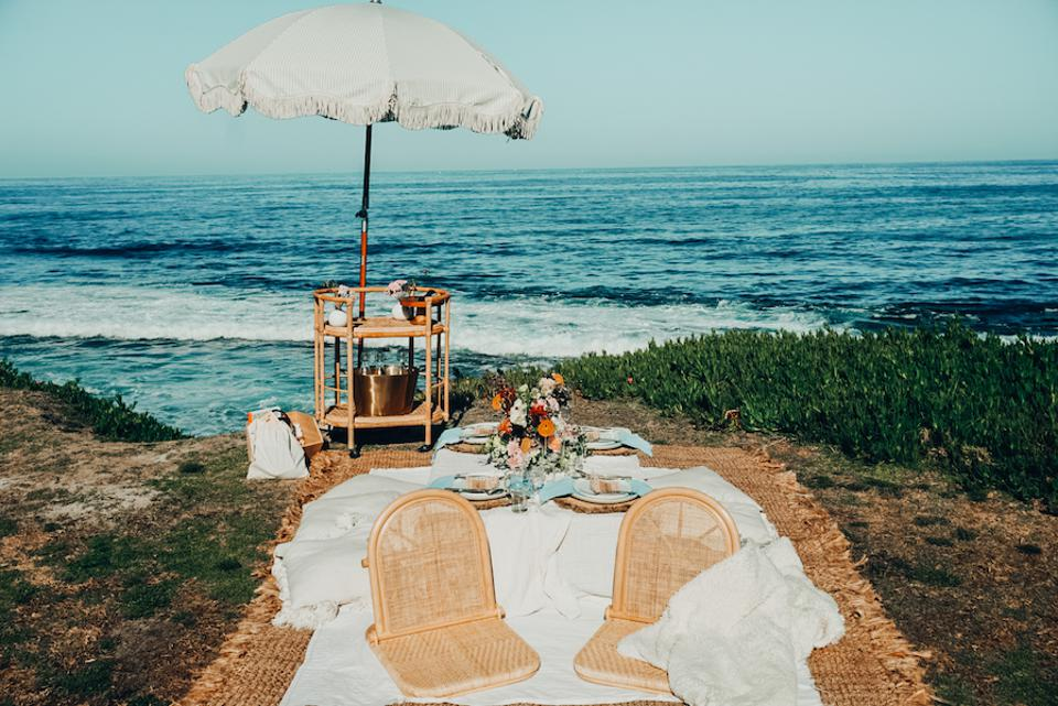 Lounge chairs and a bar cart with umbrella on the beach