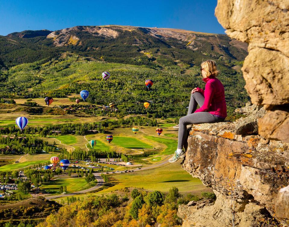 Woman sitting cliffside watching hot air balloon festival