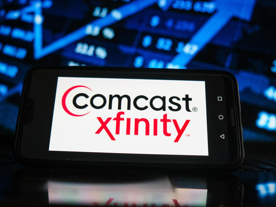In this photo illustration a Comcast logo seen displayed on...