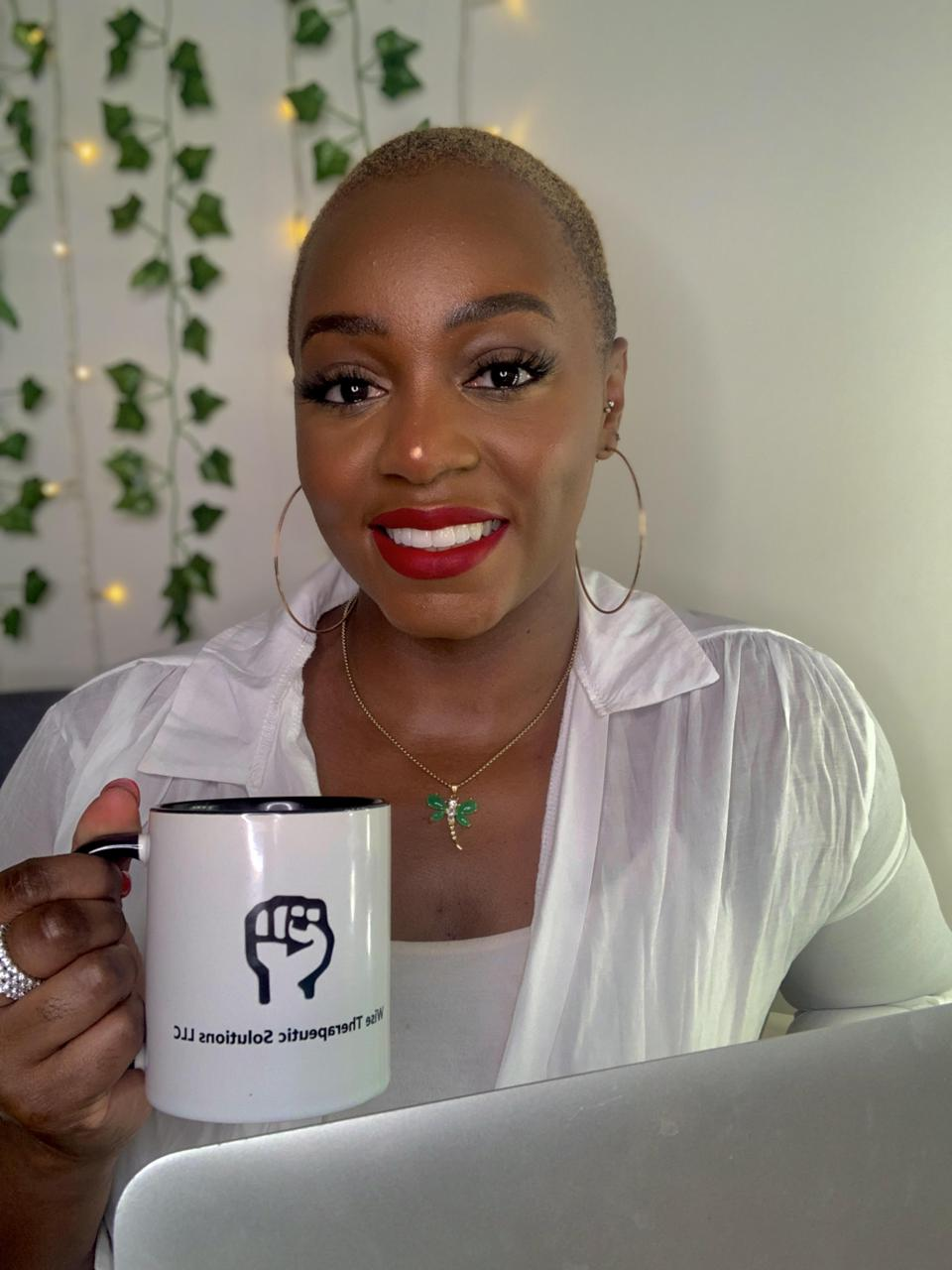 Maia Wise holding a coffee cup from her private practice, Wise Therapeutic Solutions LLC.