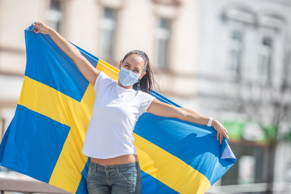 Beautiful smiling Swedish girl holds a flag while wearing a protective face mask outdoors