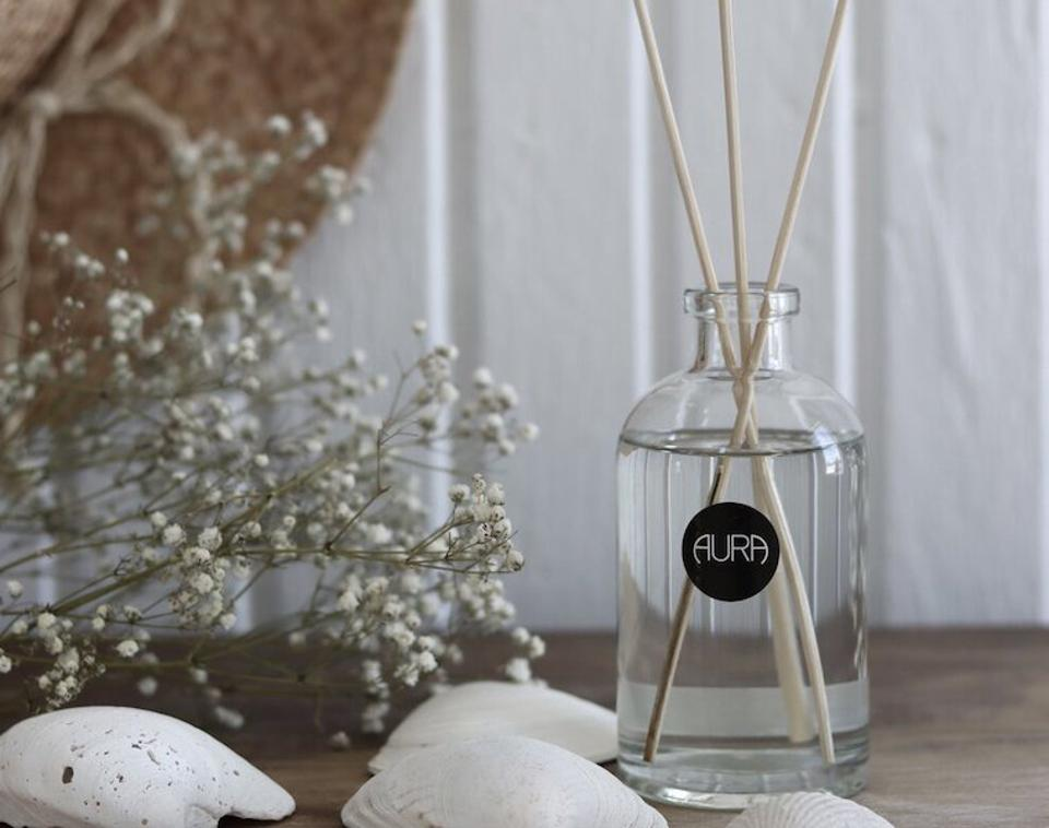 Aura reed diffuser and seashells, dried flowers against a wood background