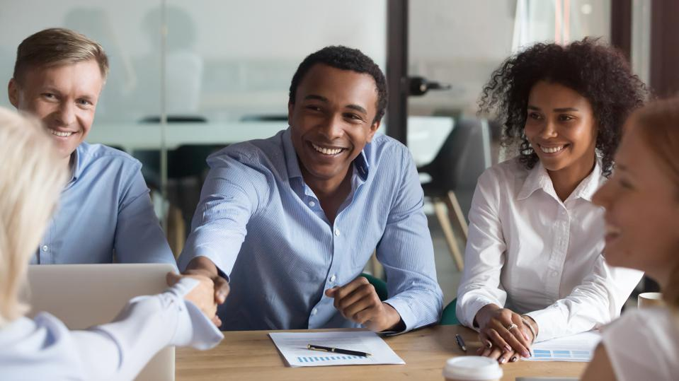 Smiling african manager handshaking  caucasian client in meeting