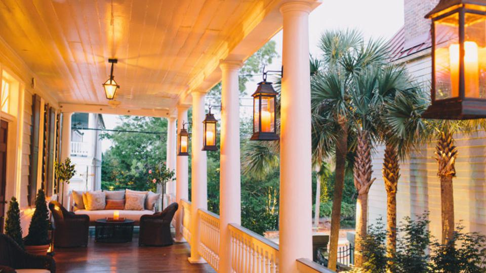 A porch with lanterns and furniture, there are palm trees in the background