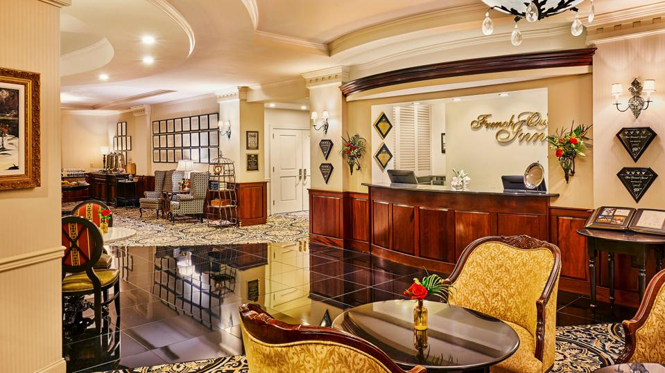 An upscale hotel lobby with a check in desk, a table and two chairs, and awards hanging on the walls
