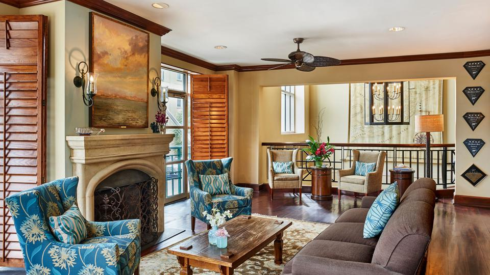 A sitting area with a fireplace framed by a large painting, and couches and a wooden table