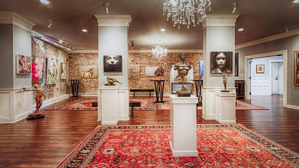 An art gallery with an ornate red rug on the floor, and a brick wall covered with detailed paintings