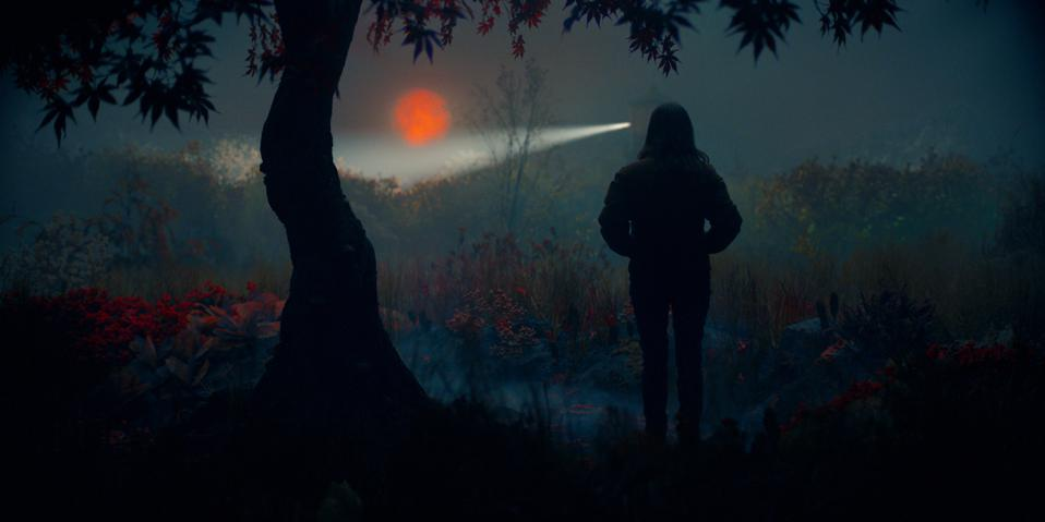 A woman's figure stands in the woods staring at the blood moon
