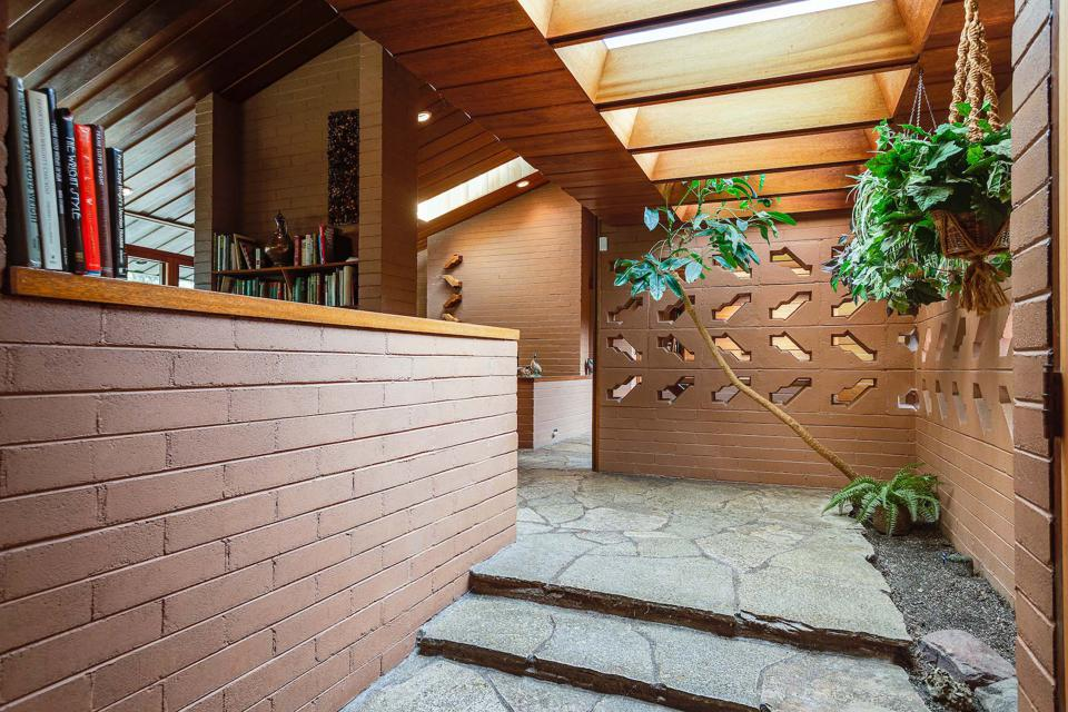 The Wright-designed original entryway features  pierced-concrete breeze blocks to allow for natural light penetration.