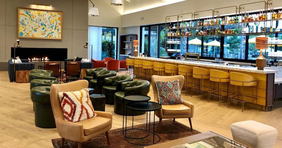 Inside of hotel lobby with a variety of seating options and a a bar