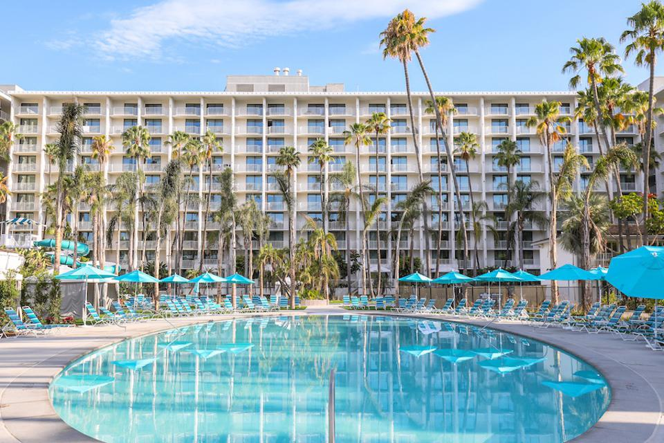 A mid century modern hotel building and pool