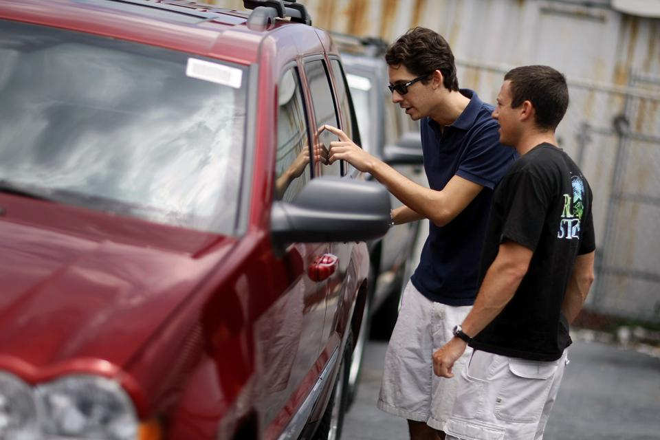 Shoppers check out a sticker price on a car dealer lot.