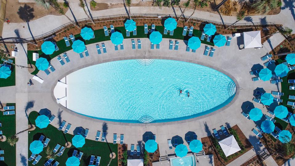 An arial view of an oval shaped pool with lounge chairs and umbrellas