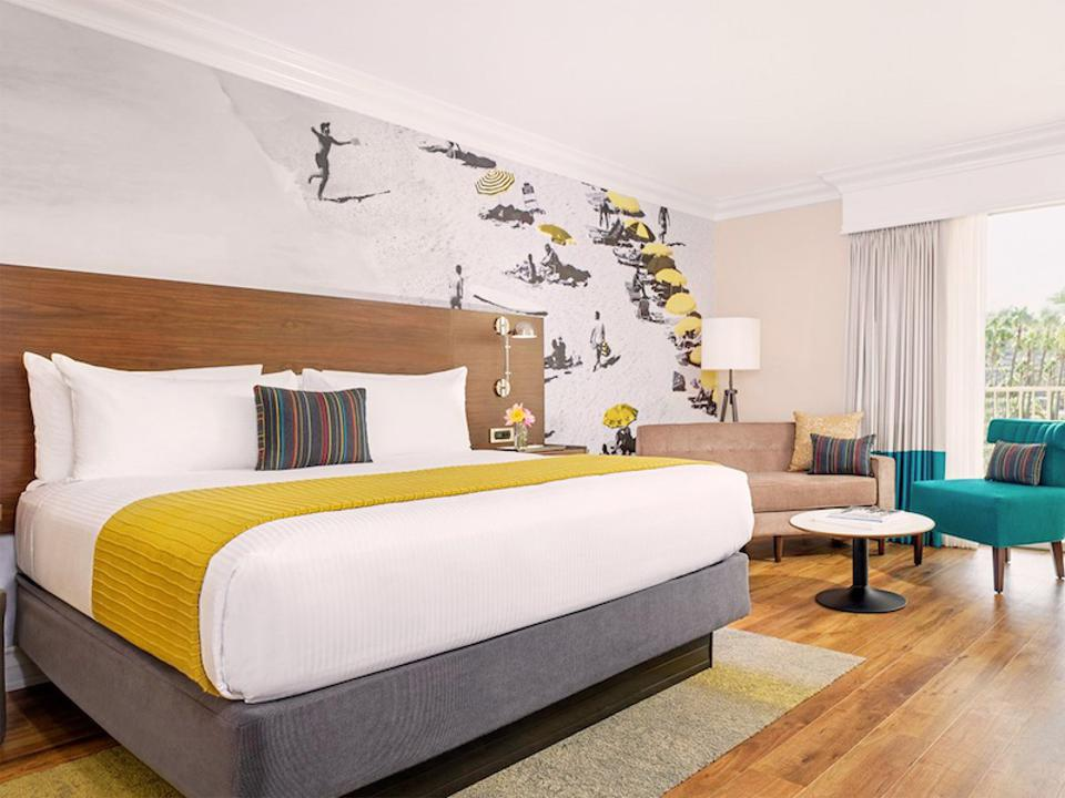 A hotel room with a bed, seating area and surf-themed mural