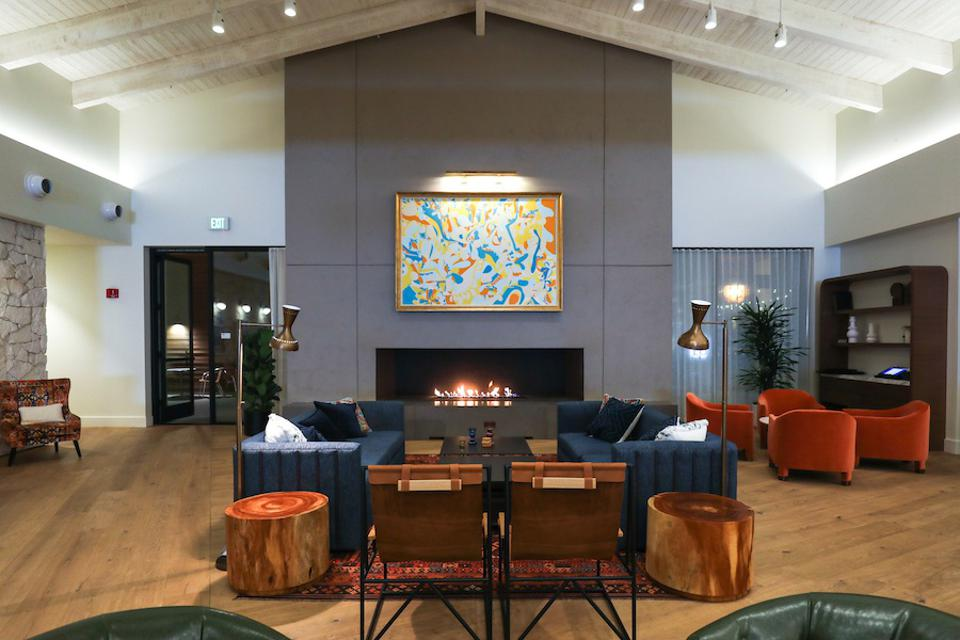 hotel lobby with beamed ceilings, stone wall and seating area
