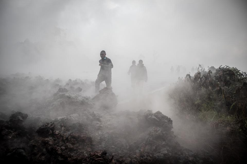 People cross cooled flows of lava near the city of Goma.