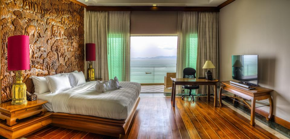 A bedroom with sea views and a carved wood wall