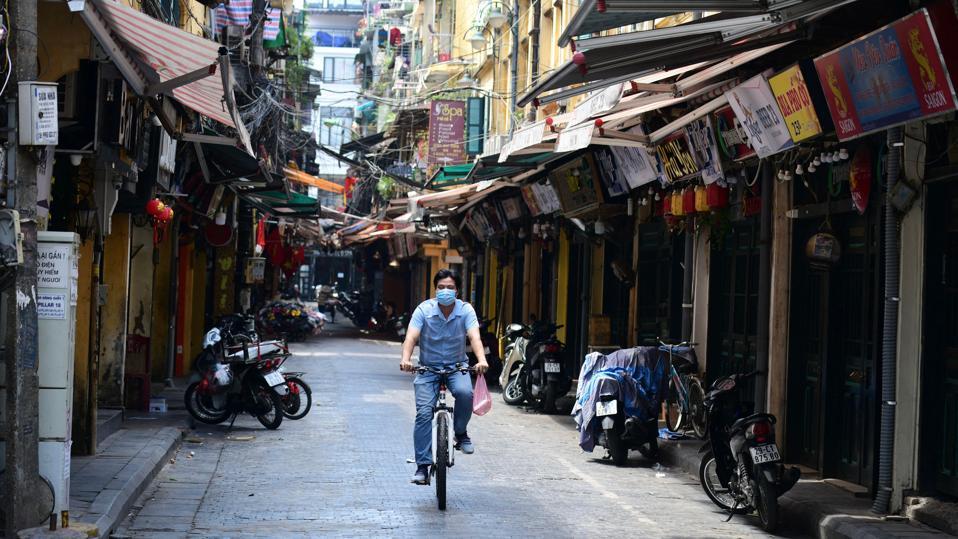 Man rides bicycle down street in Hanoi, Vietnam