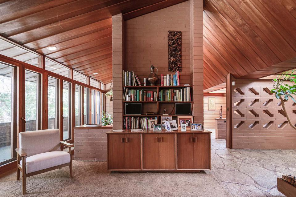 The main living room is divided by elegant built-in cabinetry and shelving.