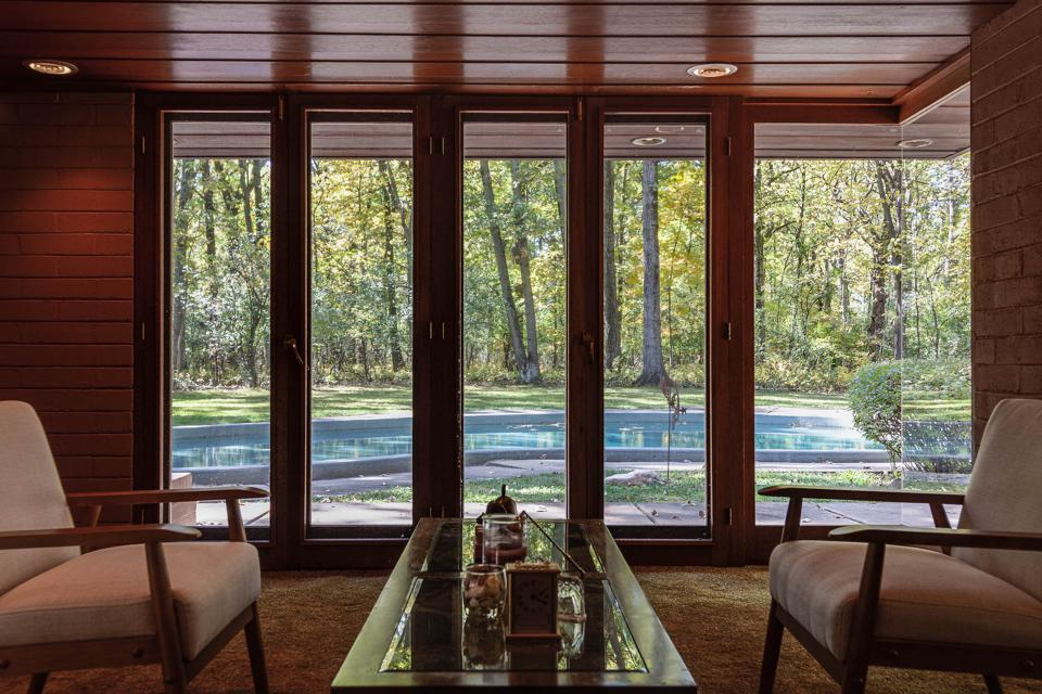 The home features expansive floor-to-ceiling windows and walls of French doors.