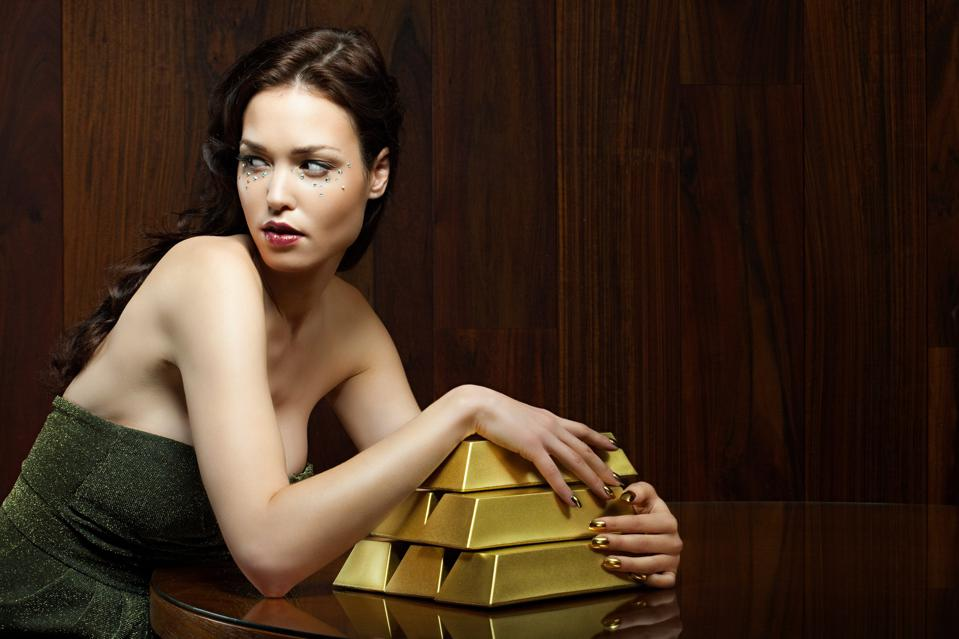 Young woman with gold ingots