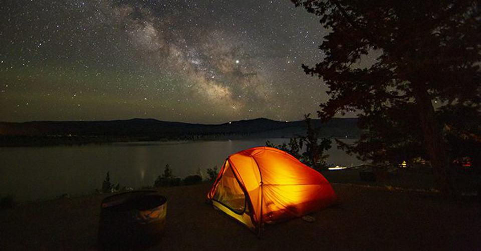 The Milky Way over Prineville Reservoir State Park and an illuminated tent.